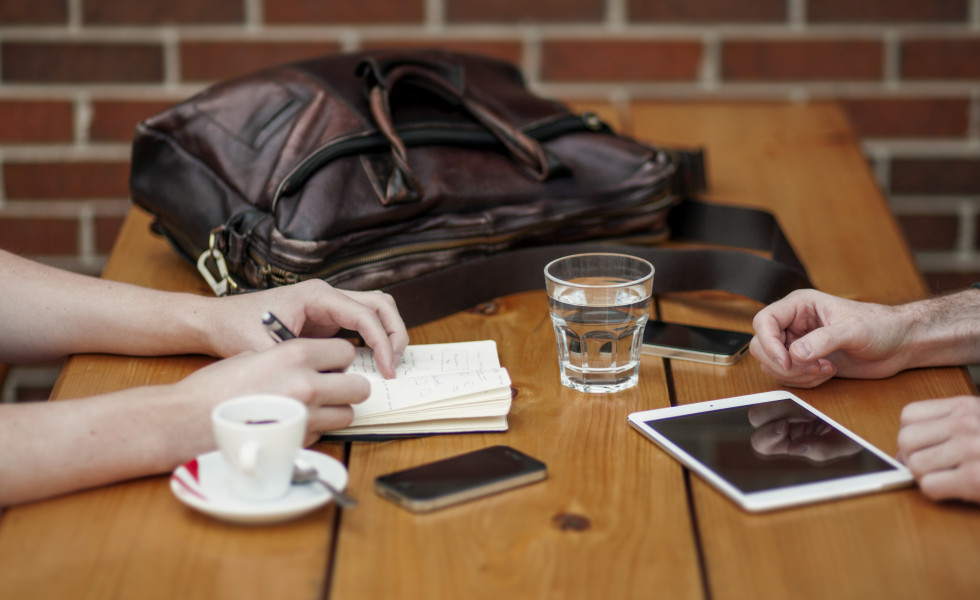 wooden table coffe tablet iphone briefcase hands